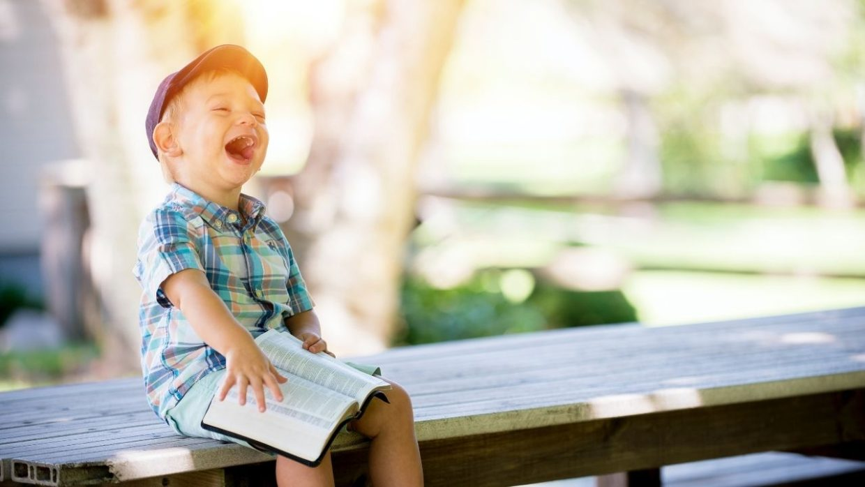 young toddler sitting on a bench while looking at a book
