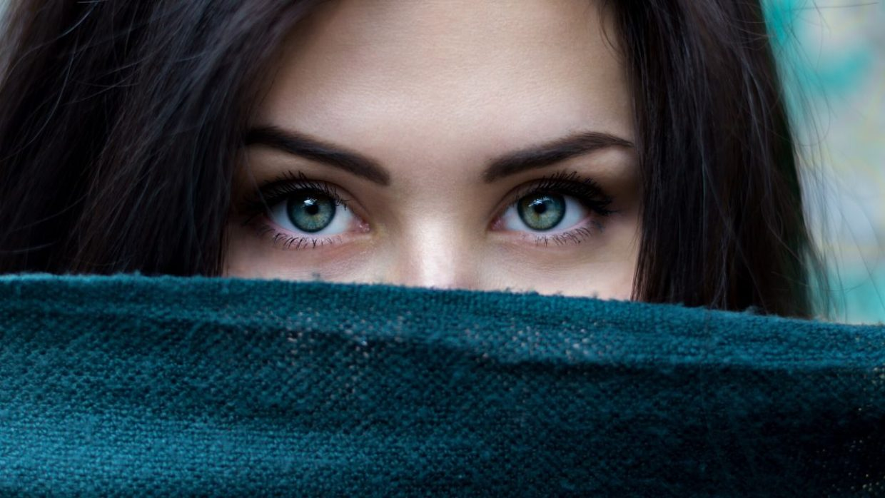 a woman's eyes looking over a piece of fabric -- wondering what is the best home remedy for dry eyes