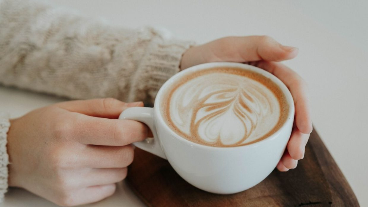 photo of someone holding a cup of coffee