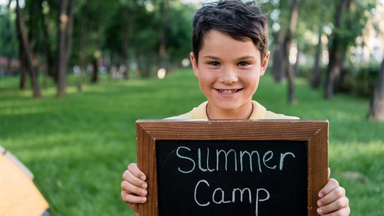 boy holding a sign - the featured image for the article on at home summer camp themes