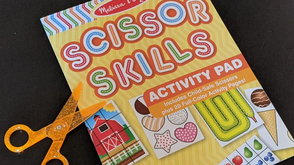 photo of a scissors skills book and a pair of scissors, which are wonderful craft supplies for toddlers just learning how to cut