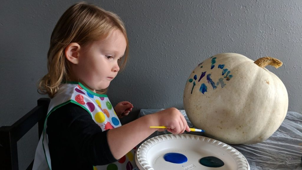 photo of my daughter painting her no-carve pumpkin