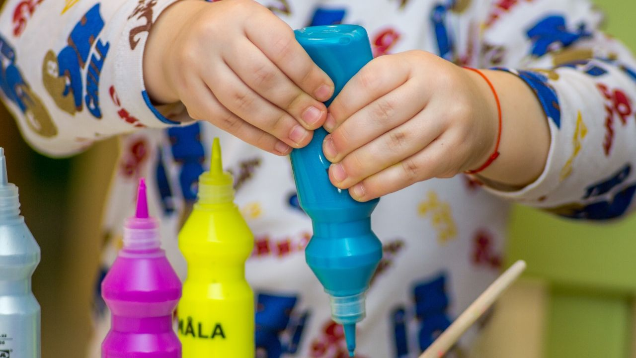 photo of a child squeezing some paint, which might come in your toddler craft subscription box