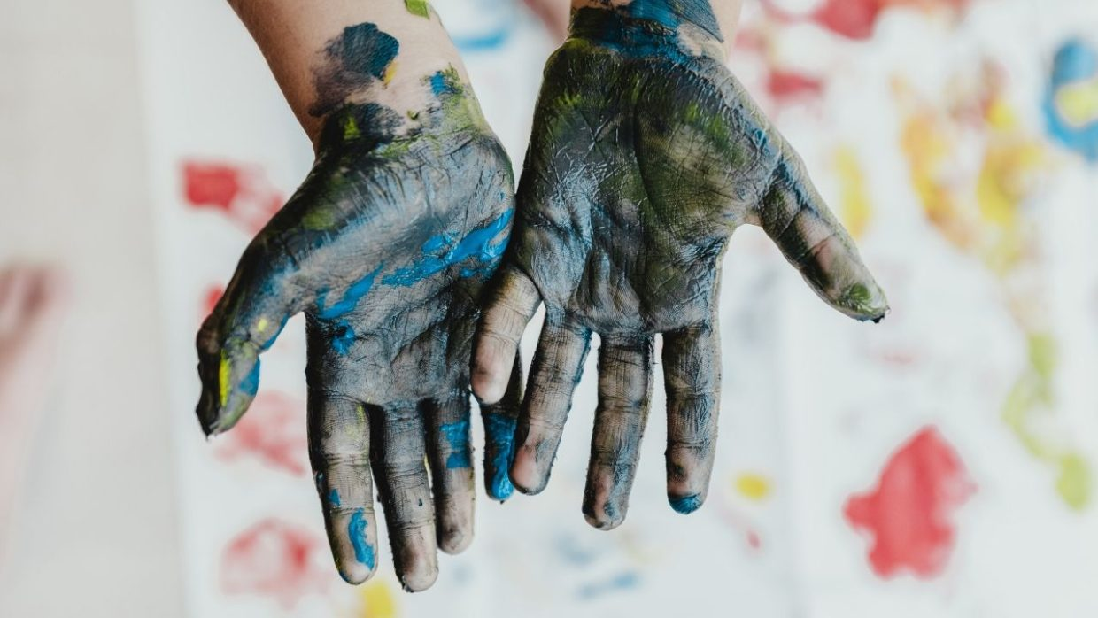 photo of a child's hands covered in paint, which is just one of the essential craft supplies for toddlers