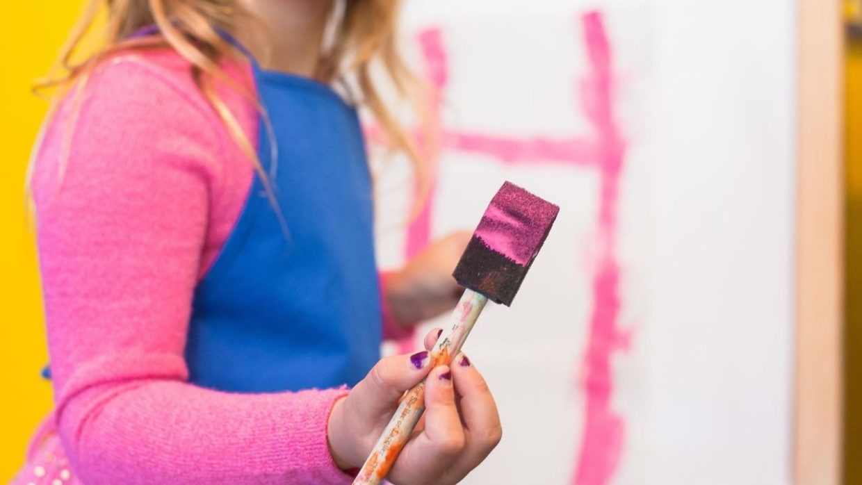 a child holding a paintbrush