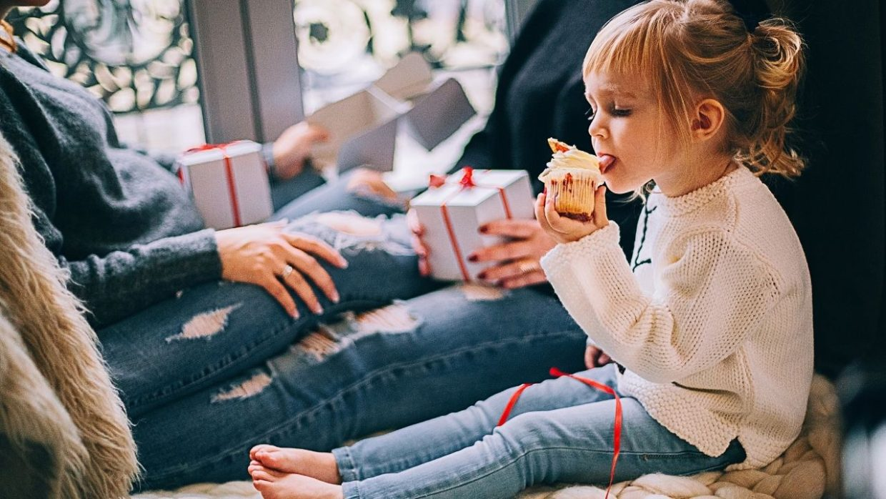 child eating a cupcake near adults holding alternative gifts for 2 year olds