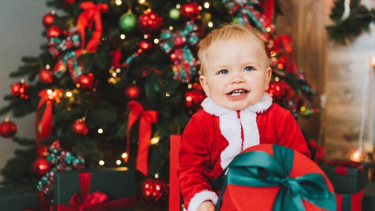 one year old holding a christmas eve box
