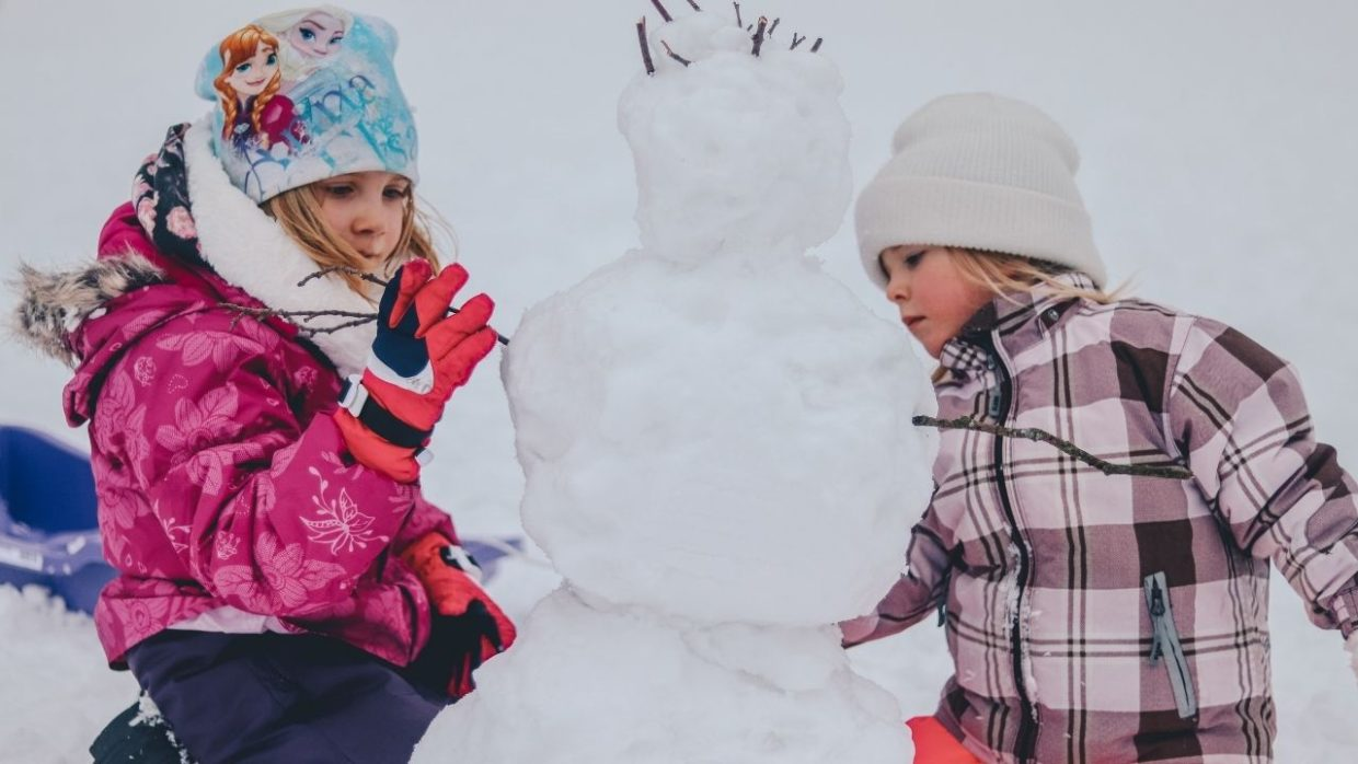 two young children building a snowman, one of the most fun winter activities for preschoolers and toddlers