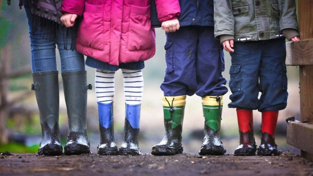children in muddy boots holding hands -- playing in the rain is just one of the fun things to do with family at home
