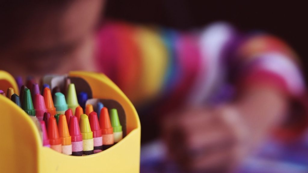 package of crayons with a child coloring in background