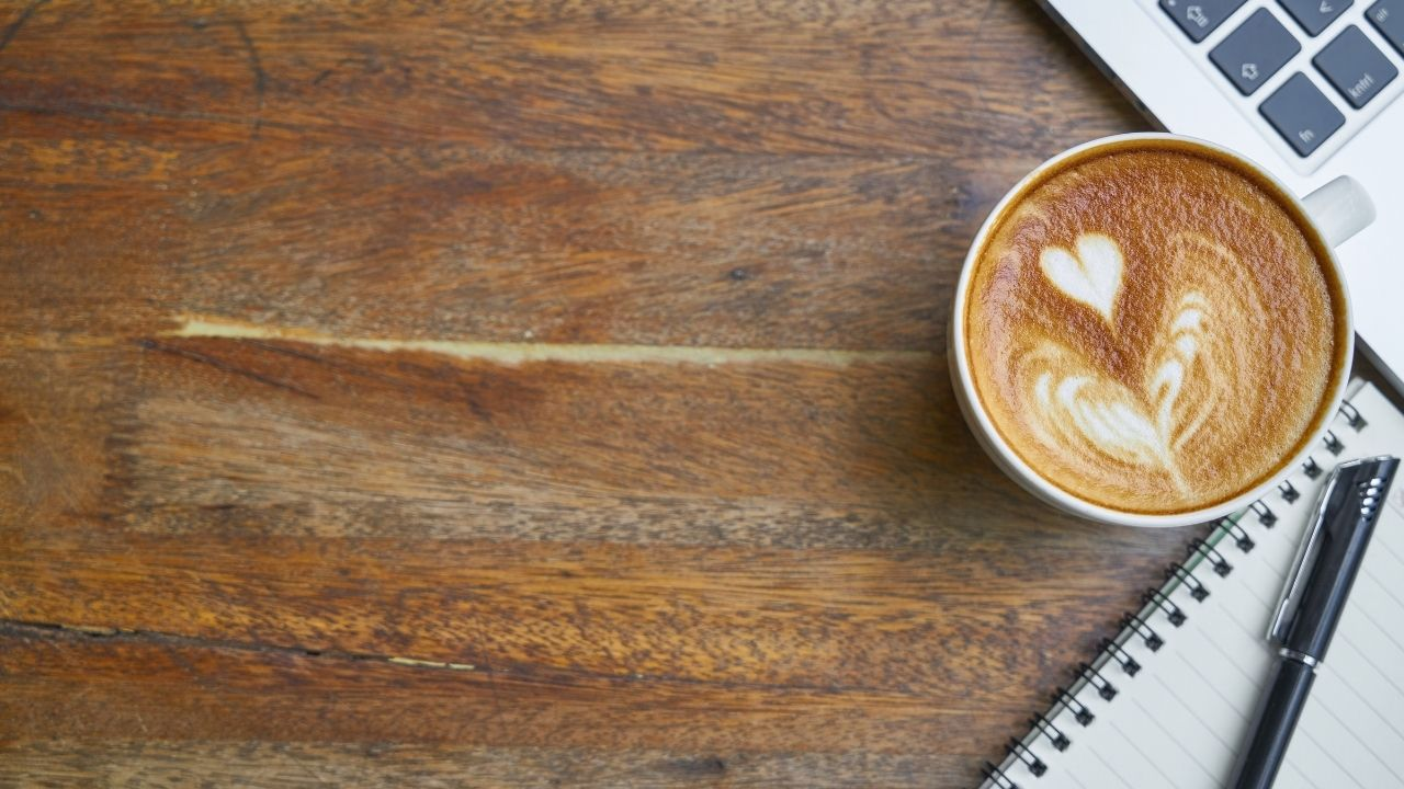notebook, coffee, and laptop on a wood surface