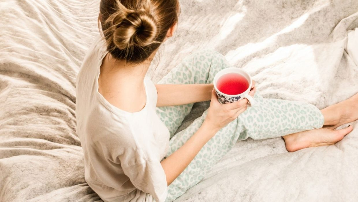 woman sitting on a bed with a cup of tea