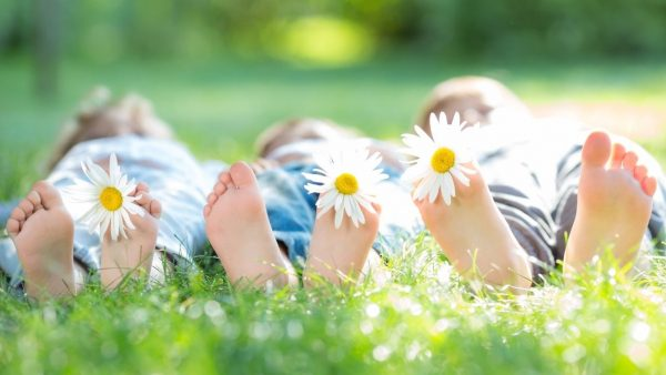 children lying on the grass with flower in their toes - a fun spring activity for families