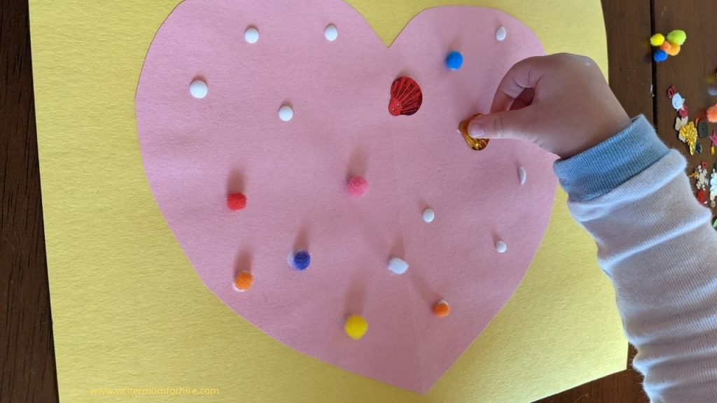 toddler placing craft supplies on a construction paper heart