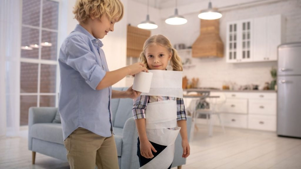 child wrapping another child in toilet paper