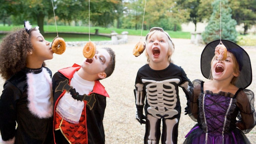 children bobbing for donuts hanging from a tree