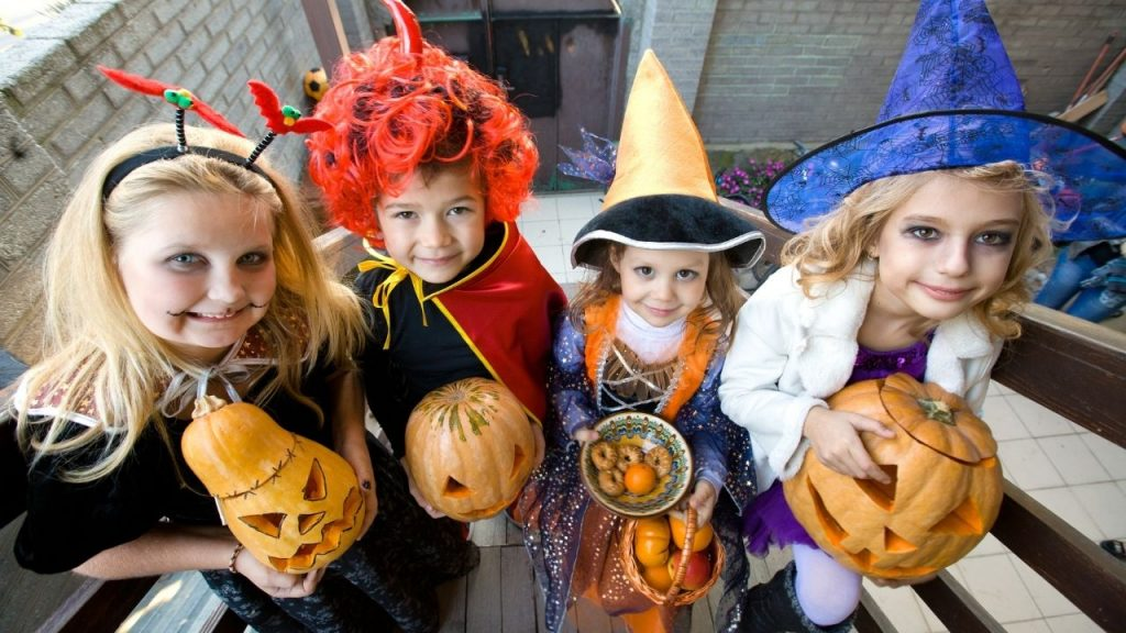 children dressed in halloween costumes holding decorated pumpkins