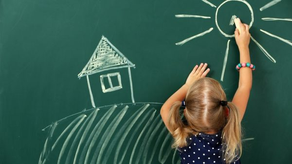 young child drawing on a chalkboard - featured image for article on what to pack for preschool