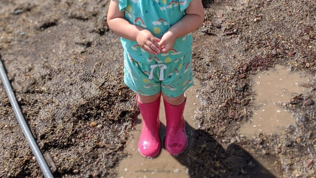 toddler wearing rain boots in the mud